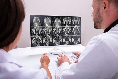 Artsen kijken naar een MRI-scan op de computer in de kliniek Stockfoto