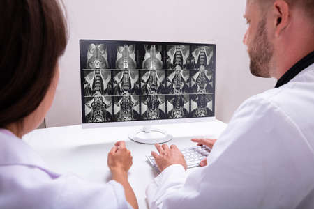 Los médicos que buscan en una resonancia magnética en el equipo en la clínica Foto de archivo