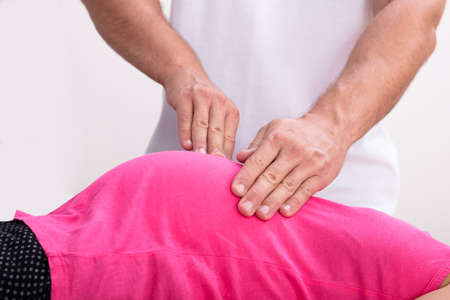 Close-up Of Male Physiotherapist Massaging Tummy Of Pregnant Woman Stockfoto