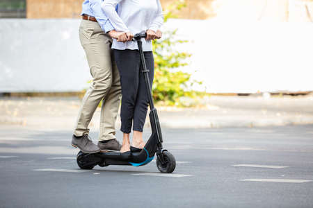 Portrait Of Happy Couple Riding On Electric Scooter Over The Street In The City