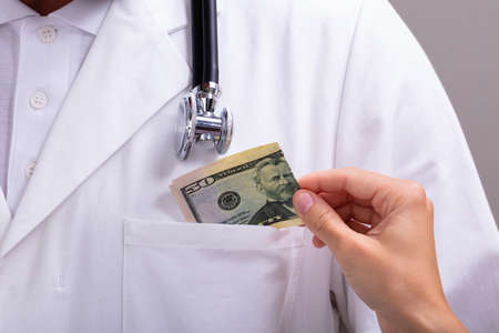 Close-up Of A Medicinal Male Doctor Receiving Dollar Banknote As A Bribe In Clinic