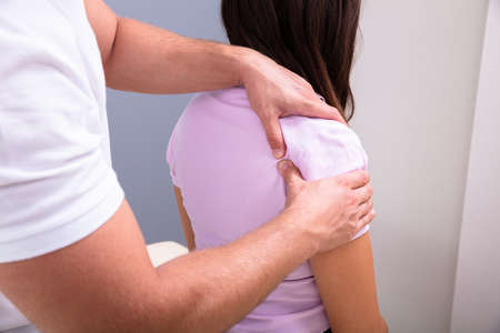 Professional Male Physical Therapist Massaging The Injured Shoulder Of A Woman Slowly In Medical Clinic Zdjęcie Seryjne
