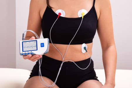 Mujer vistiendo un dispositivo de monitor Holter para el seguimiento diario de un electrocardiograma