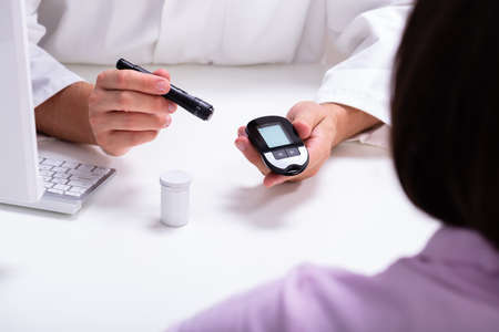 Doctor Showing Lancet Pen And Digital Glucometer To Woman For Checking Blood Sugar Level