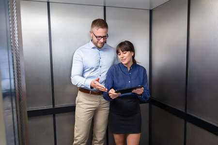 Portrait Of A Businessman And Businesswoman Standing In Elevator Discussing The Project On Digital Tablet Фото со стока