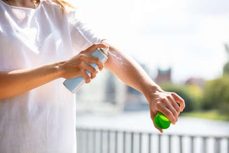 Close-up de la mano de una mujer rociar el aerosol Deet anti insectos en la piel al aire libre