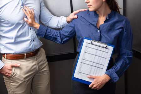 Close-up Of A Businessman Sexually Harassing Female Colleague By Touching Her Shoulder