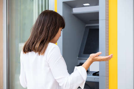 Close-up Of Disappointed Young Woman Looking At ATM Bank Machine After Checking The Account Balance