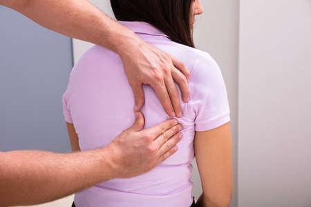 Close-up de un fisioterapeuta masculino dando masaje de espalda al paciente sentado en la clínica