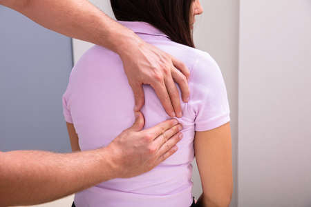 Close-up Of A Male Physiotherapist Giving Back Massage To Female Patient Sitting In Clinic