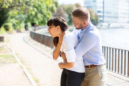Mann hilft erstickender Frau, einen eingeklemmten Gegenstand aus den Atemwegen zu vertreiben. Heimlich-Manöver Standard-Bild