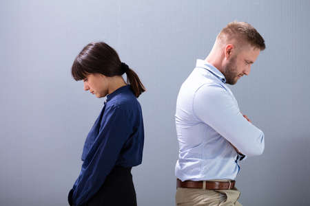 Side View Of A Depressed And Sad Couple Ignoring Each Other Standing Back To Back