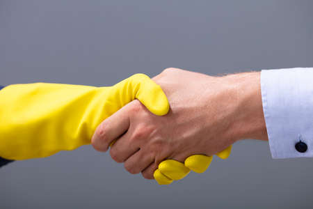 Close-up Of Businessman And Janitor Shaking Hands Together Against Gray Background