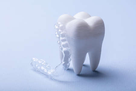 Close-up Of Transparent Mouth Guard And White Tooth Model On Blue Backdrop