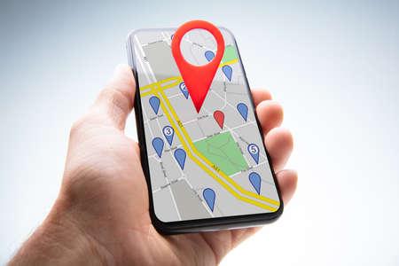 Close-up of a Person's Hand Holding Cellphone avec pointeur de carte rouge sur fond blanc