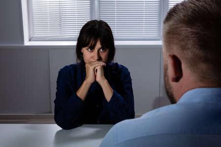Hombre sentado delante de una mujer joven preocupada triste que sufre de depresión mirando hacia otro lado
