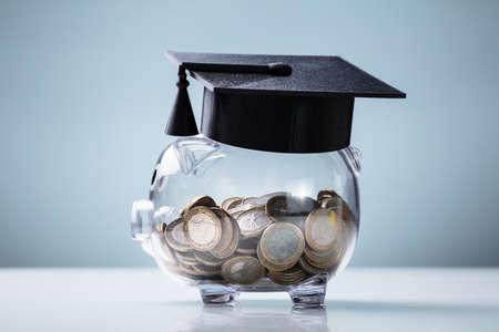 Cappello da laurea nero con salvadanaio trasparente disposto su scrivania bianca su sfondo blu