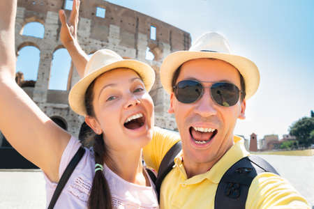 Couple Taking Selfie In Front Of Colosseum, Rome, Italy