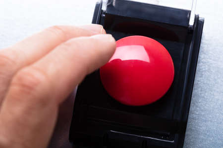 Close-up Of Person's Hand Emergency Bell On Table