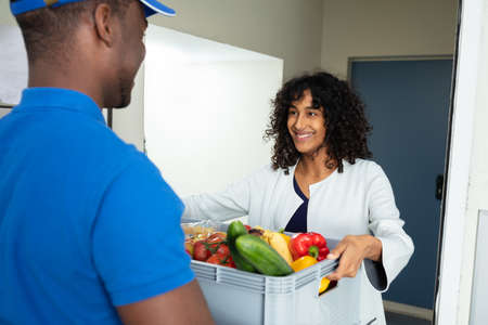 Mujer sonriente recibiendo entrega de comestibles en casa