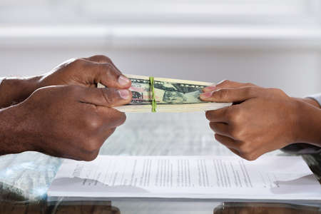 Couple Hands Holding Currency Over The Divorce Agreement