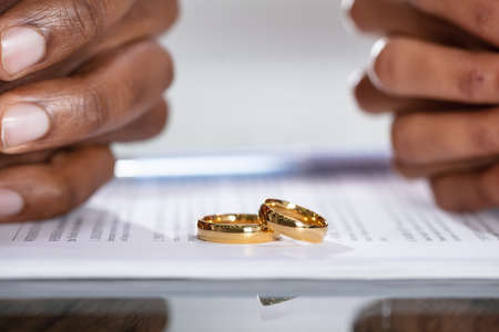 Couple Hands On Divorce Agreement Near Wedding Rings Stock Photo