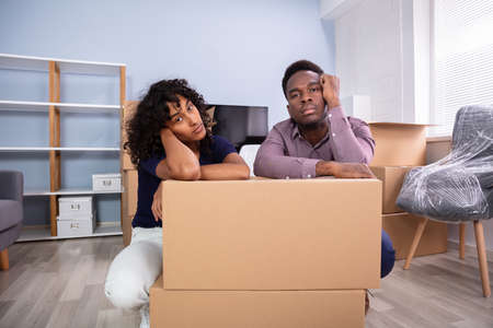 Stressed Couple Sitting Near Boxes In New Home