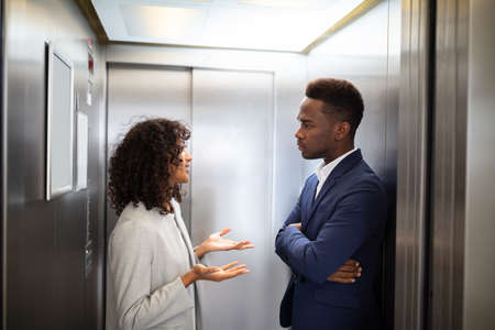 Young African Businesspeople Having Conversation In Elevator