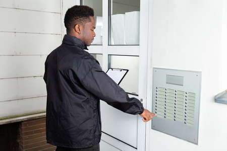 Man Standing In Front Of The House Knocking The Door Stock fotó
