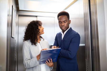 Businesspeople Discussing Standing Inside Elevator At Work Banque d'images