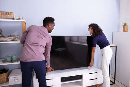 Side View Of Young Couple Lifting Television At Home