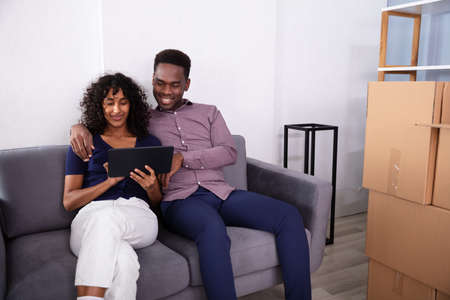Young Couple Sitting On Couch Using Tablet Inside Their New Home