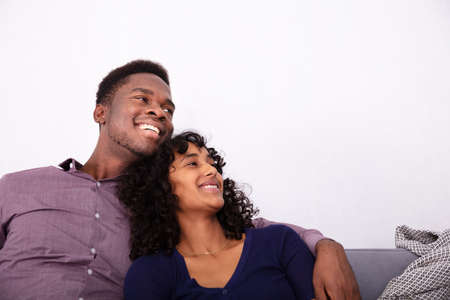 Laughing Couple Sitting On Sofa At Home Stock Photo