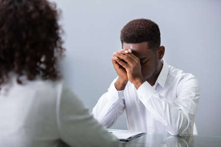 Stressed Young Business Man Holding His Head At Interview In Office