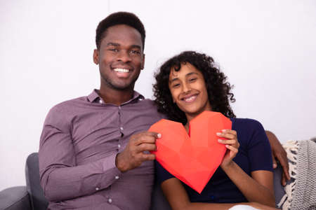Romantic Couple Holding A Red Heart At Home
