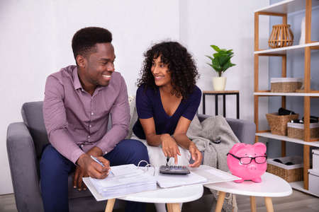 Young Couple Sitting On Sofa Calculating Invoices At Home