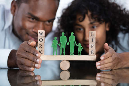 Young Couple Protecting Work And Life Balance On Seesaw Stock Photo
