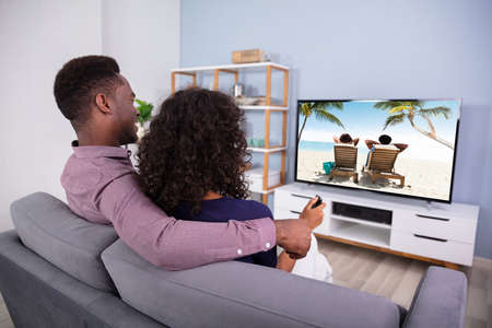 Affectionate Young Family Watching TV At Home