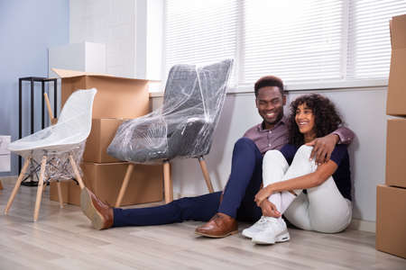 Young Couple Sitting On Floor Inside Their New Home Stock Photo