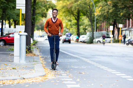 Young African Man Riding An Electric Scooter
