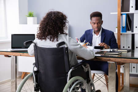 Businesswoman Sitting In Wheelchair Working In Office Фото со стока