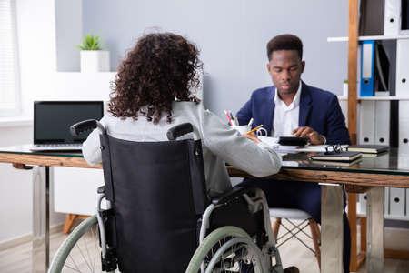 Businesswoman Sitting In Wheelchair Working In Office Archivio Fotografico
