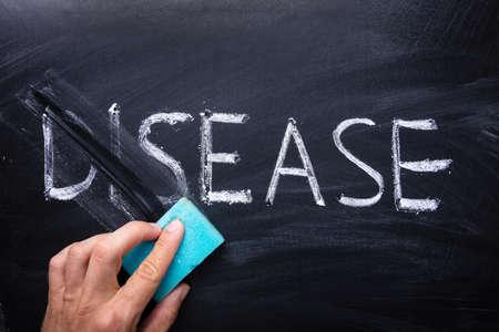 Person's Hand Erasing The Word Disease With Blue Sponge Written On Chalkboard Stock Photo