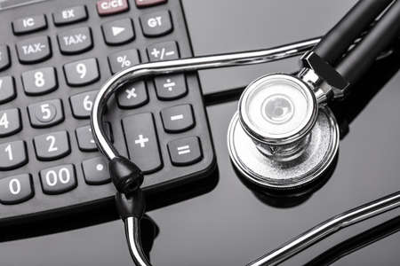 An Overhead View Of Stethoscope And Calculator Over Black Background
