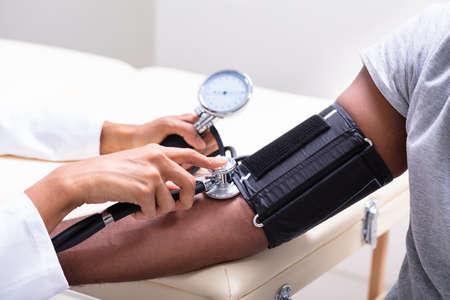 Close-up de la mano de la doctora controlando la presión arterial