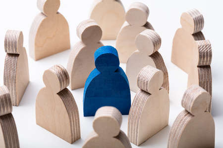 Close-up Of A Blue Human Figure Surrounded With Wooden Figures Over White Desk