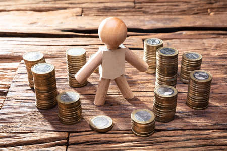 Stacked Golden Coins Around By Wooden Human Figure Over Desk