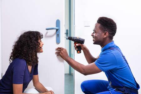 Technician Fixing The Door Lock At Clients Home Stock Photo