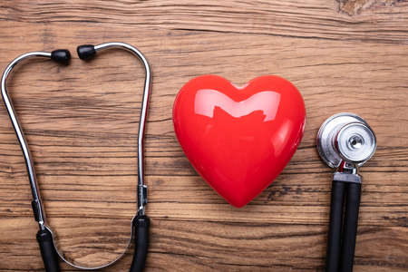 High Angle View Of Stethoscope Arranged Near Red Heart Against Wooden Table