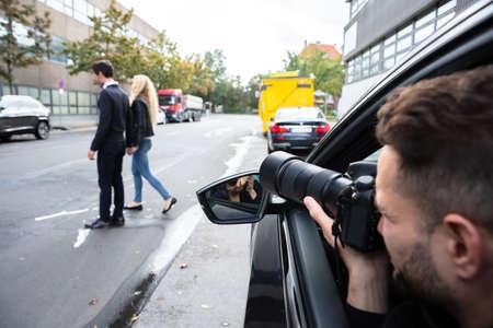 Jonge mannelijke spion zit in de auto en maakt een foto van een paar dat op straat loopt